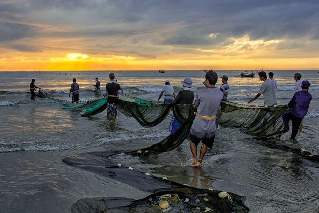 Fishermen-casting-fishing-net-at-dawn-in-My-Khe-Beach